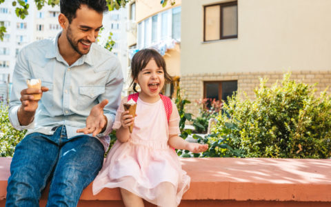 Image of happy cute little girl sitting with dad on the city street and eating ice-cream outdoor. Fun girl kid and father have fun and playing outside. Good relationship between dad and daughter