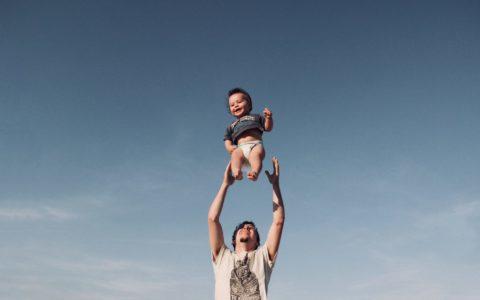 photo-of-man-in-raising-baby-under-blue-sky-1166990