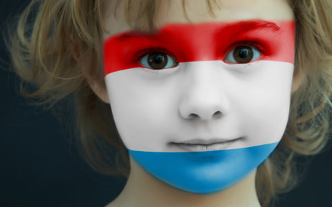 Portrait of a child with a painted flag of Luxembourg on her face, closeup.